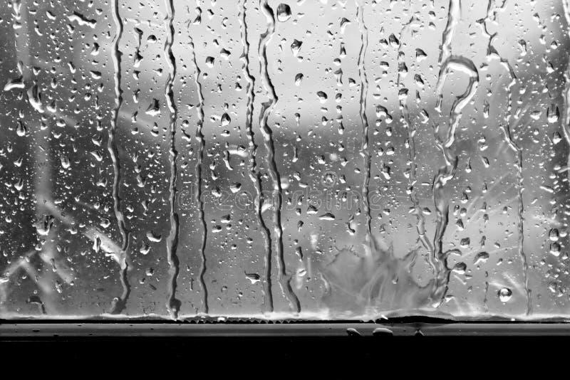 Mörk regndroppe för bakgrund på grå färger för fönsterexponeringsglas arkivfoto