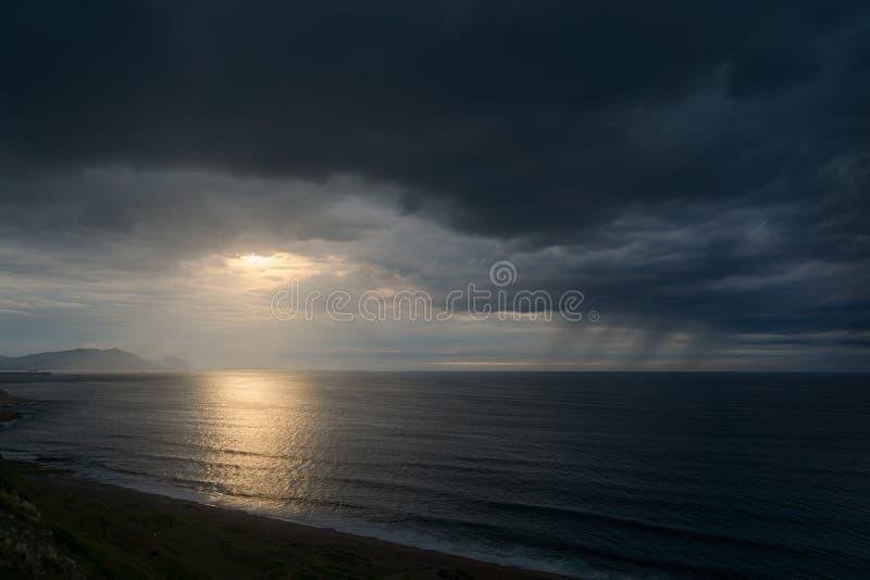 Mörk seascape med stormiga moln på solnedgången arkivbild