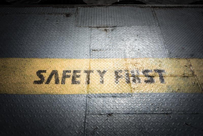 Mörk signal för tappning av det första tecknet för säkerhet på gul linje på metall royaltyfri foto