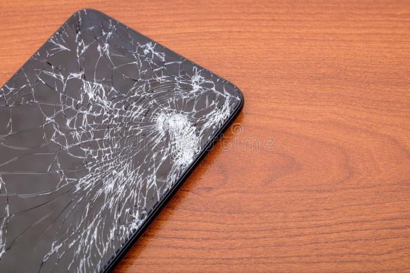 Mörk smartphone med den brutna pekskärmen på träbakgrund royaltyfri foto