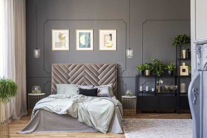 Mörk sovruminre med en väl till mods dubbelsäng, affischer, svart sh royaltyfria foton