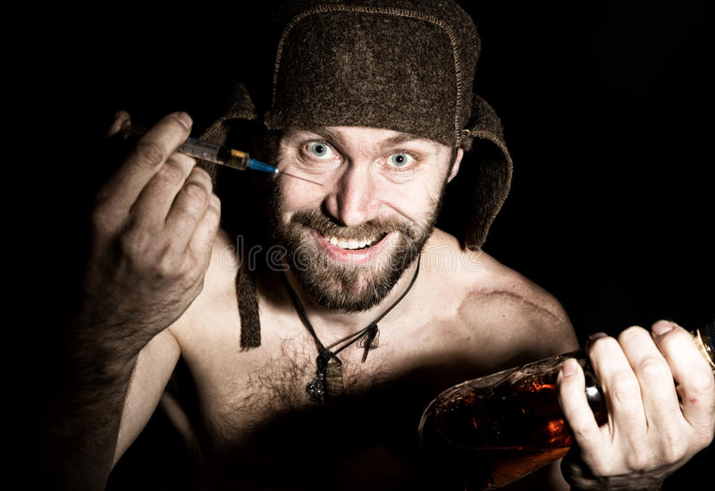 Mörk stående av den läskiga onda illavarslande skäggiga mannen med flin, erbjudanden en variation av droger, en injektionsspruta  arkivbilder