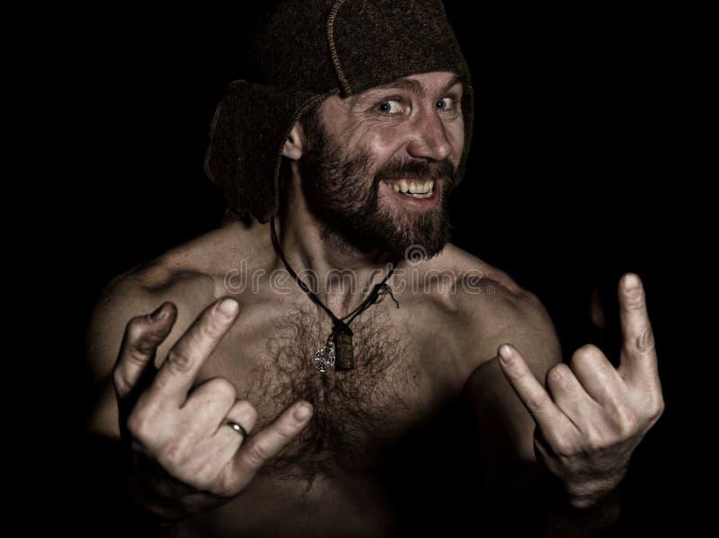 Mörk stående av den läskiga onda illavarslande skäggiga mannen med flin, showtecken av heavy metal konstig rysk man med ett naket arkivbilder
