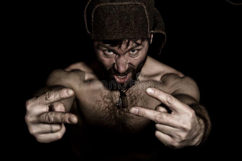 Mörk stående av den läskiga onda illavarslande skäggiga mannen med flin, showtecken av segern konstig rysk man med ett naket royaltyfria bilder