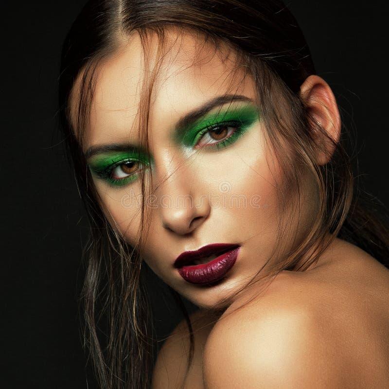 Mörk ståendebrunettflicka med grön makeup royaltyfria foton