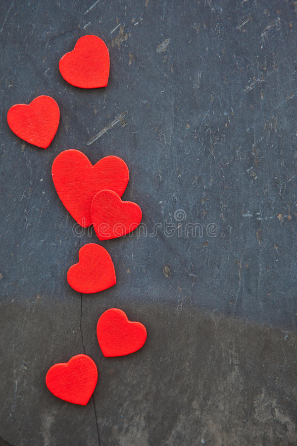 Mörk stenbakgrund med hjärtor arkivbilder