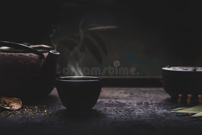 Mörk tebakgrund med den asiatiska tekannan för svart järn och att råna av varmt te med ånga på tabellen royaltyfria foton
