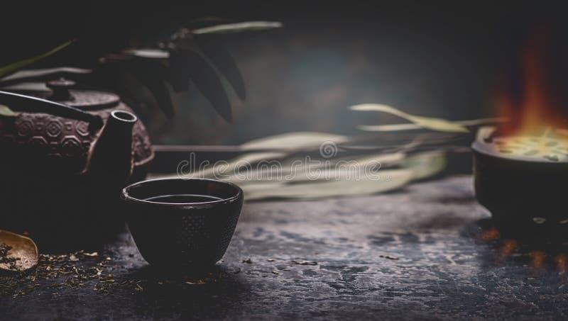 Mörk tebakgrund med den asiatiska tekannan för svart järn och att råna av varmt te på tabellen på den mörka väggen kopieringsutry royaltyfri fotografi
