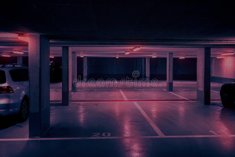 Mörk underjordisk bil som parkerar däcket med neonrött ljus royaltyfri fotografi