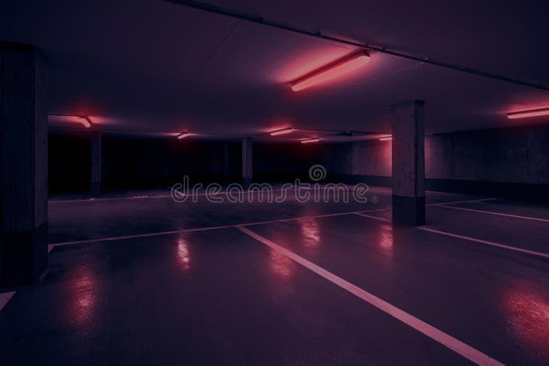 Mörk underjordisk bil som parkerar däcket med neonrött ljus fotografering för bildbyråer