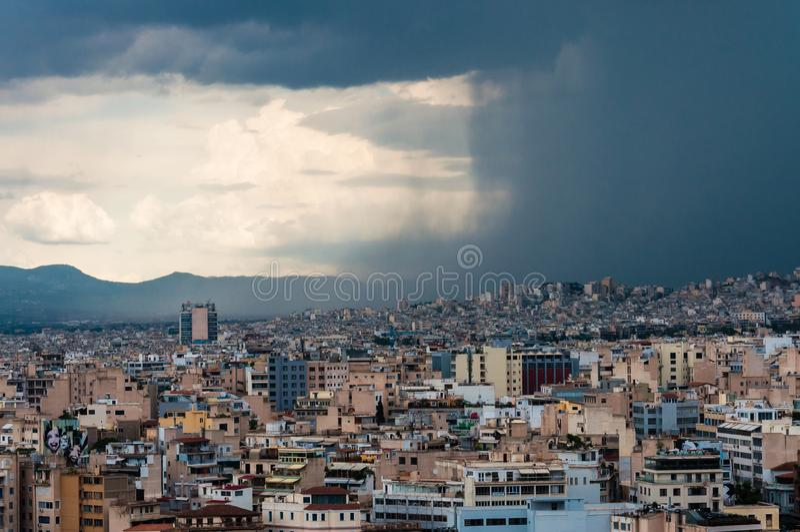 Mörk vägg för kontrast av fallande vatten från den lynniga himlen av den kommande stormen på staden Panorama- cityscapesikt på Gr royaltyfri fotografi