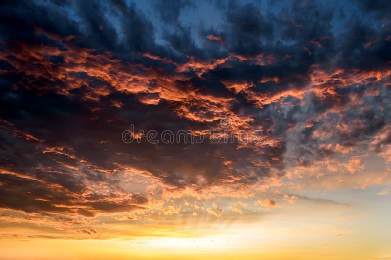 Mörka åskmoln med röda orange reflexioner av inställningssolen Sceniska stormmoln som tänds av de sista strålarna av solnedgången royaltyfria foton