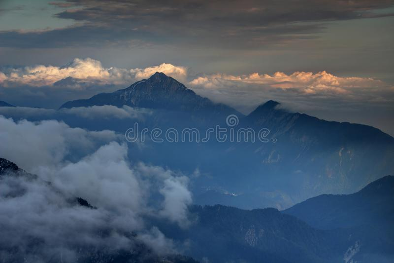 Mörka berg, höstmist och solbelysta moln i slovenska fjällängar arkivfoton
