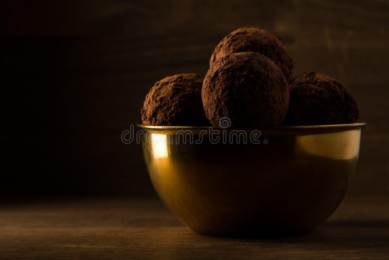 Mörka chokladtryfflar i guld- bunke på träbakgrund, härligt guld- ljus royaltyfri foto