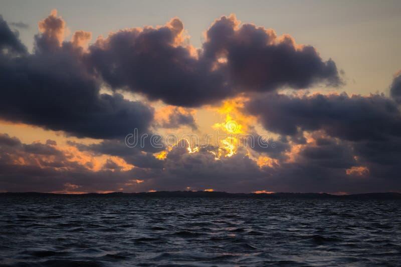 Mörka dramatiska solnedgångmoln över havsvatten Aftonlandskap s royaltyfri foto