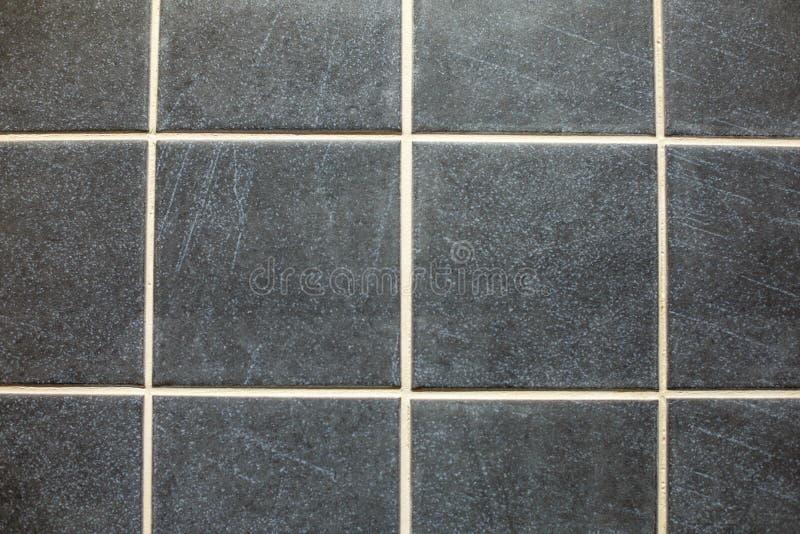 Mörka grå färgtegelplattor på golvet arkivbild