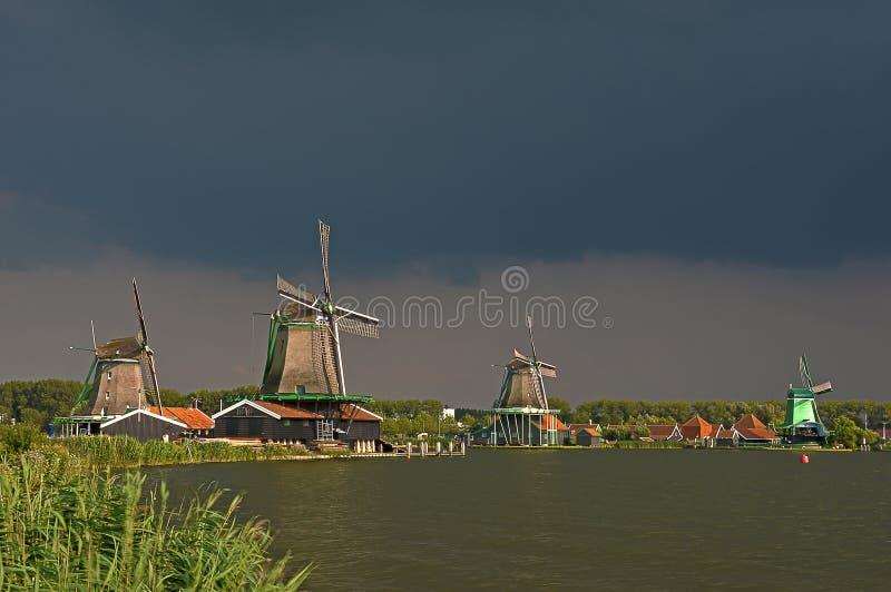 Mörka himlar över Zaanse Schans väderkvarnar royaltyfria bilder