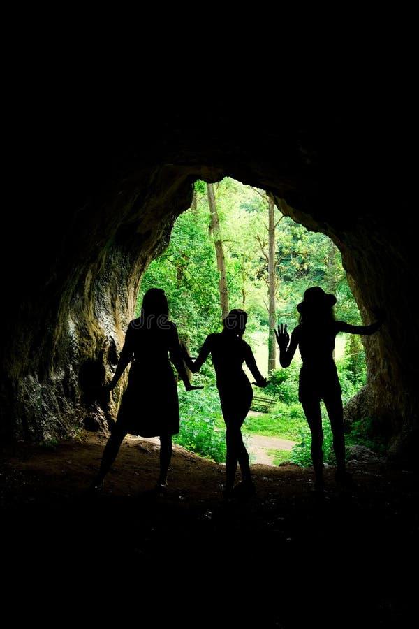 Mörka kvinnliga konturer på ingången till den naturliga grottan royaltyfri foto
