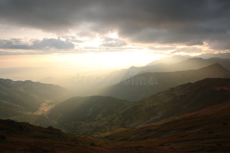 Mörka moln över bergen på soluppgång arkivbilder