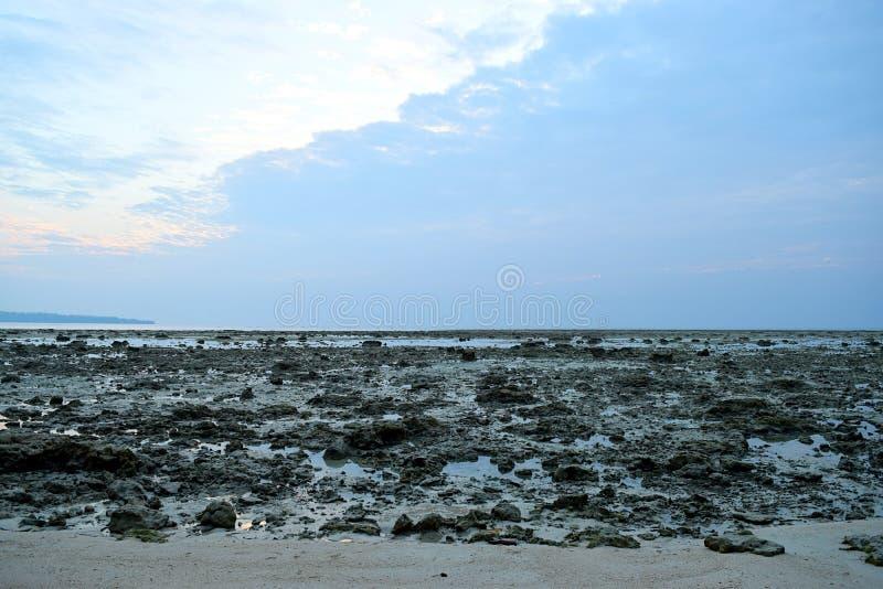 Mörka och ljusa sidor - himmel på skymning över en Rocky Beach - naturlig bakgrund royaltyfria bilder