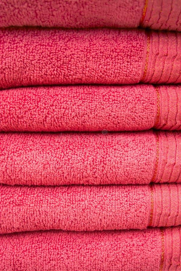 Mörka rosa badrumhanddukar i bunten, brunnsortbegrepp fotografering för bildbyråer