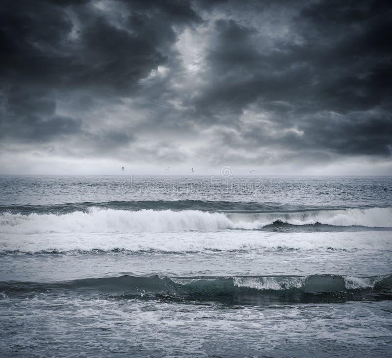Mörka stormiga himmel- och havsvågor royaltyfria foton