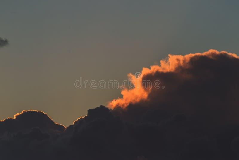 Mörka stormiga moln som täcker himlen vid solnedgång arkivfoto
