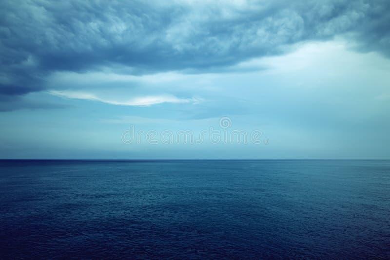 Mörker - blått hav och stormiga moln arkivbilder