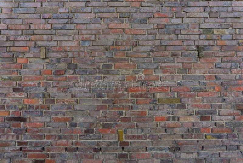 Mörker - den röda tegelstenväggen texturerar arkivfoto
