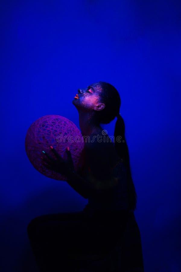 Mörker för flickasammanträdeprofil under UV ljus med bollen royaltyfria foton