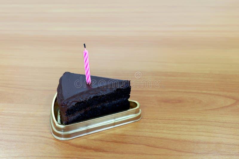 Mörker för HBD-kakachoklad halvmånformig för 1 stycke som blåser kakastearinljusbrunt, lycklig födelsedag en årsårsdag på tabellt royaltyfri foto
