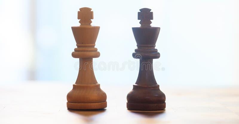 Mörker för schackstycken, ljus - brun färg Övre sikt för slut av konungar med detaljer suddighet bakgrund arkivbild