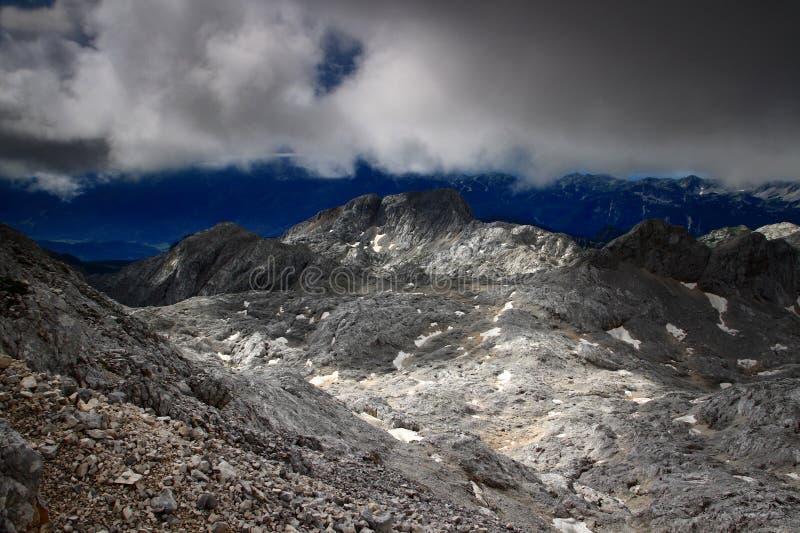Mörker fördunklar över den steniga Hribarice platån, Julian Alps, Slovenien royaltyfri bild