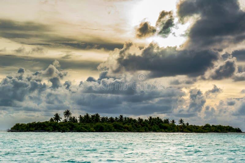 Mörker fördunklar att sväva över himlen under solnedgången ovanför den tropiska ön royaltyfri bild