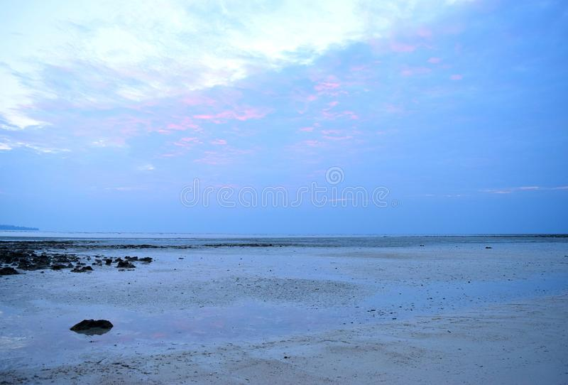Mörker fördunklar, ljus himmel och orange färger av solnedgången över havet på Serene Secluded Beach - fridsamt ställe - slutet a arkivbild