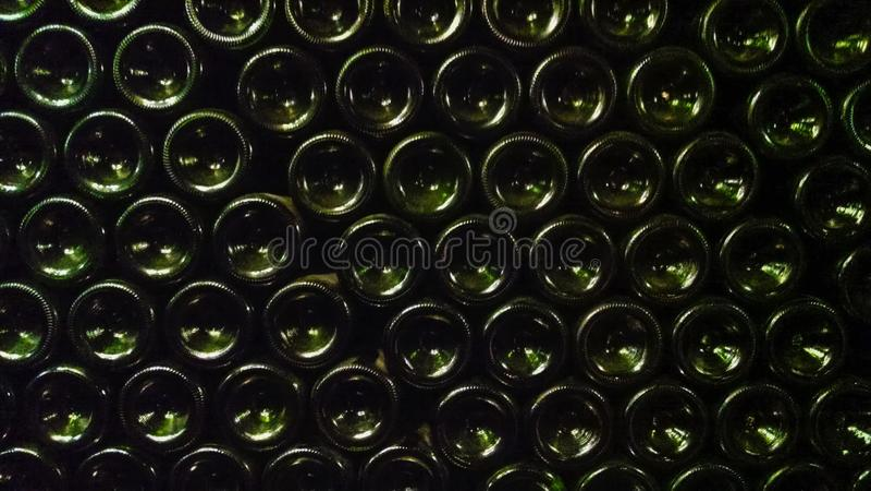 Mörker - gröna ölflaskor som upp till staplas, bildar en vägg arkivbild