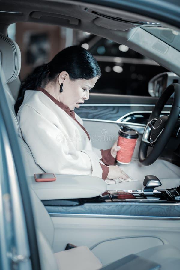 Mörker-haired affärskvinna som bär det beigea laget som spiller hennes kaffe på det royaltyfria bilder