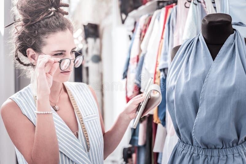 Mörker-haired bärande exponeringsglas för modeformgivare som tänker om ändrande tyg arkivbild