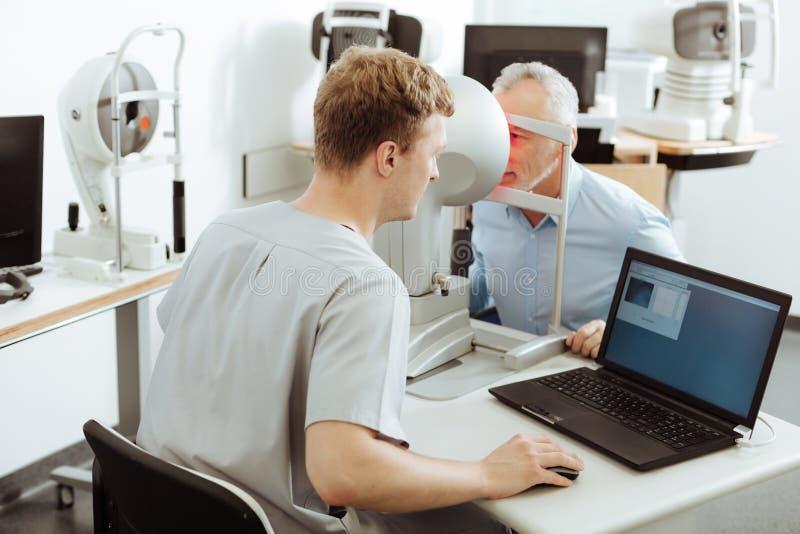 Mörker-haired bärande likformig för ögondoktor som talar till patienten arkivfoto