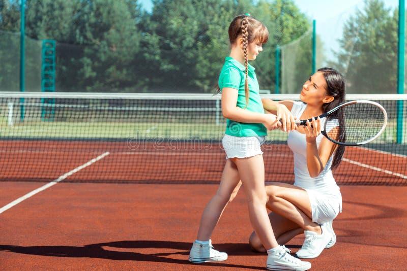 Mörker-haired flicka som lyssnar till hennes mamma, innan att spela tennis arkivfoto
