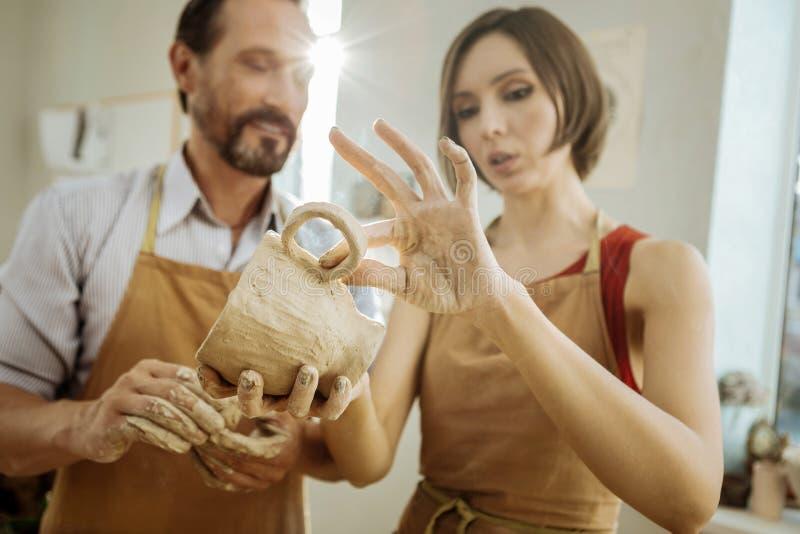 Mörker-haired kvinnlig ceramist som förbättrar hennes framtida tekopp fotografering för bildbyråer