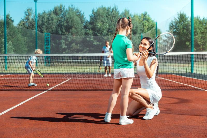 Mörker-haired mamma som ler, medan undervisa flickan som spelar tennis arkivfoto
