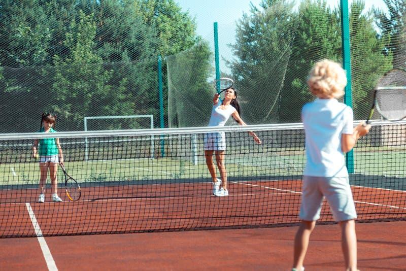 Mörker-haired moder som spelar tennis med barn på helgen arkivfoton