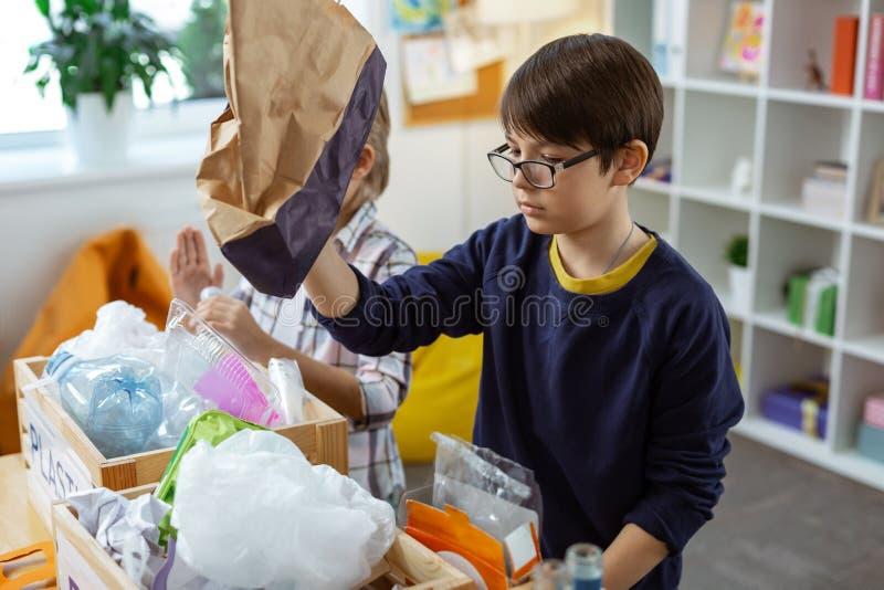 Mörker-haired nätt pojke observera den pappers- påsen i hans händer arkivbild