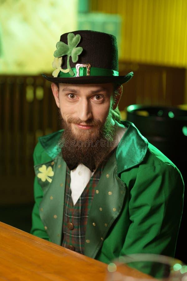 Mörker-haired skäggig ung man i en grön dräkt som sitter på tabellen i ett kafé royaltyfri foto