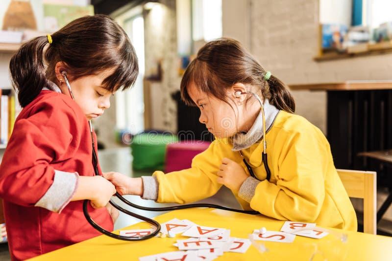 Mörker-haired soliga barn som lär bokstäver och tillsammans spelar arkivbilder
