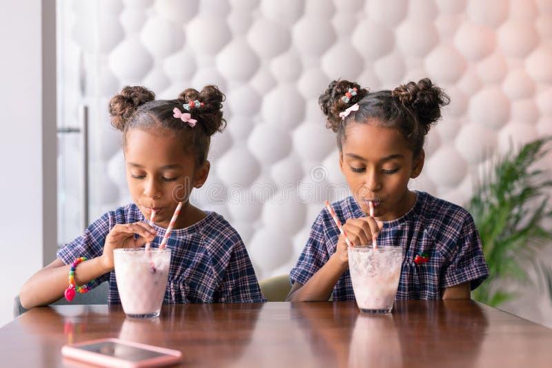 Mörker-haired systrar som bär ljusa hårspännar som tycker om deras milkshakar royaltyfri foto