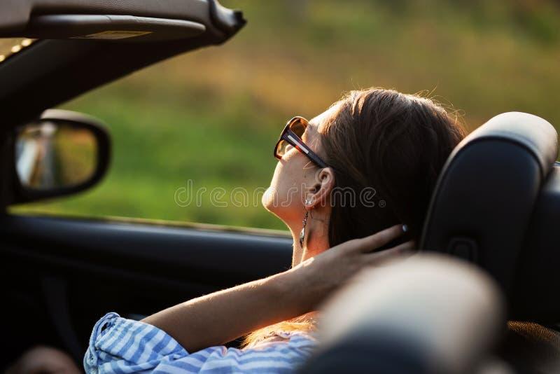 Mörker-haired ung kvinna i solglasögon som sitter i gig på solig dag royaltyfri bild
