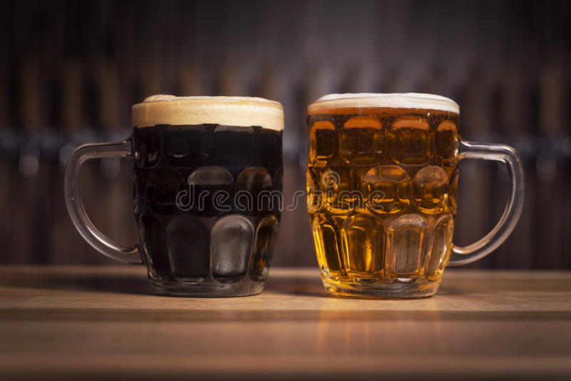 Mörker- och cleeröl i ett stort öl rånar ställningar på stången arkivfoto