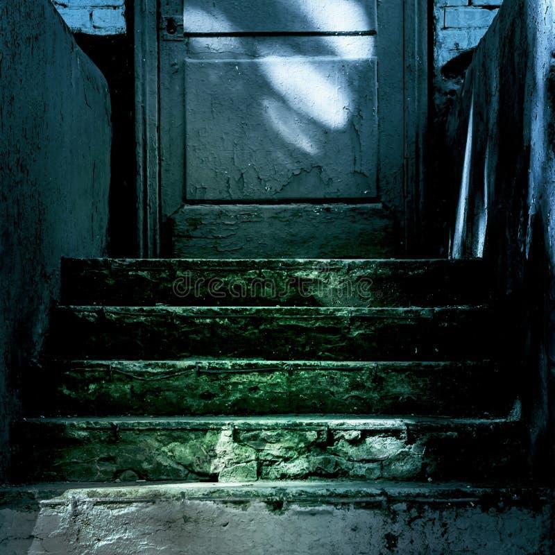 Mörker och fasa på den stängda ingångsdörren till spökehuset Mörker stenar den förstörda gamla trappuppgången från källaren med fotografering för bildbyråer